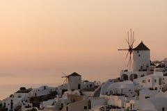 在白色风车的惊人的日落在Oia和全景镇到圣托里尼海岛,锡拉,希腊 免版税图库摄影