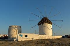 在白色风车的日落在米科诺斯岛,基克拉泽斯海岛上  库存照片