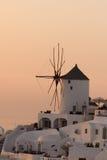 在白色风车的日落在Oia和全景镇到圣托里尼海岛,锡拉,希腊 免版税库存照片