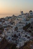 在白色风车的日落在Oia和全景镇到圣托里尼海岛,锡拉,希腊 免版税库存图片