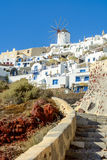 在白色风车的看法和Oia镇传统建筑学圣托里尼海岛的 免版税库存图片