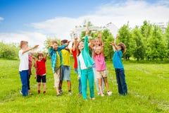 在白色飞机玩具以后的愉快的孩子伸手可及的距离 库存照片