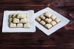 在白色餐巾,木背景的白色巧克力 免版税库存照片