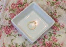 在白色首饰盘子的简单的金单粒宝石定婚戒指在v 图库摄影