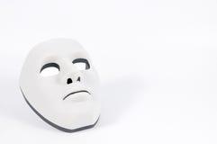 在白色,人类行为后掩藏的黑面具 库存图片