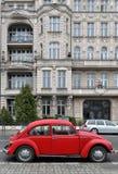 在白色经典老大厦的红色汽车背景甲虫 库存照片