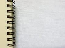 在白色织品背景的笔记本 库存照片