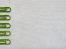 在白色织品背景的绿色夹子 库存图片