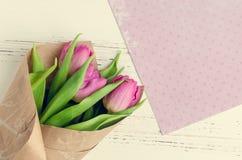在白色破旧的别致的背景的桃红色郁金香 免版税库存照片