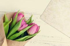 在白色破旧的别致的背景的桃红色郁金香 免版税库存图片