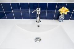 在白色水槽的卫生间龙头 库存图片