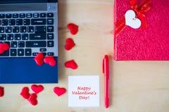 在白色贴纸写的愉快的华伦泰` s天文本,个人计算机,红色笔,在木桌上的红色心脏装饰的礼物盒在办公室 库存照片