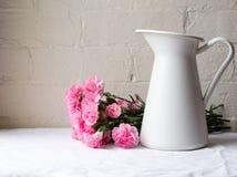 在白色水罐后的桃红色康乃馨 免版税库存图片