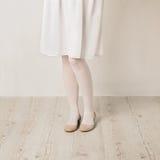 在白色贴身衬衣、裙子和芭蕾舱内甲板的女性腿在白色b 图库摄影