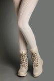 在白色贴身衬衣和明亮的冬天起动的女性腿 免版税库存照片