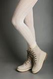 在白色贴身衬衣和明亮的冬天起动的女性腿 库存照片