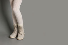 在白色贴身衬衣和明亮的冬天起动的女性腿 图库摄影