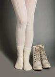 在白色贴身衬衣和明亮的冬天起动的女性腿 库存图片