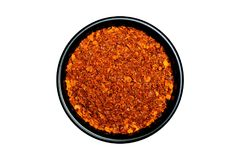 在白色b隔绝的一个黑碗的热的红辣椒粉末 免版税图库摄影