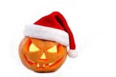 在白色ba的万圣夜南瓜发光的里面佩带的圣诞节帽子 免版税库存图片