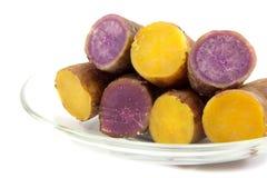 在白色backgrou的板材煮沸的煮沸的紫色和黄色薯类 免版税库存图片