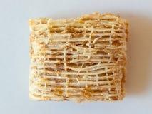 在白色backgroun的麦子方形的早餐谷物极端特写镜头 免版税库存照片