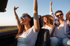 在白色T恤打扮的深色头发的年轻女人有朋友的黑敞蓬车坐一个夏日 库存图片