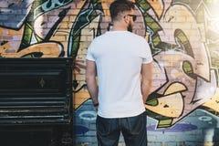 在白色T恤杉打扮的有胡子的行家人是反对墙壁的立场有街道画的 嘲笑 商标的,文本,图象空间 免版税库存图片