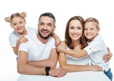在白色T恤杉拥抱的微笑的家庭 免版税库存照片