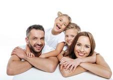 在白色T恤杉拥抱的微笑的家庭 免版税图库摄影