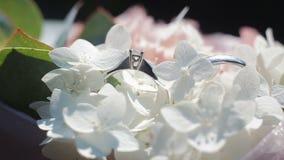 在白花花束的婚戒  婚戒的转动的白色和桃红色花构成和花束  股票录像