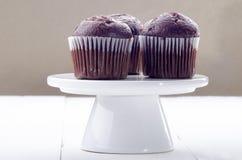 在白蛋糕立场的巧克力松饼 免版税库存照片