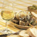 在白酒调味汁和根菜类的蛤蜊壳为杯白葡萄酒面包切片和橄榄服务 图库摄影