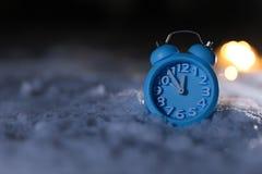 在白雪,文本的空间的闹钟和圣诞灯 午夜读秒 图库摄影