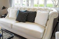 在白革的白色和蓝色枕头在客厅横卧 免版税库存图片
