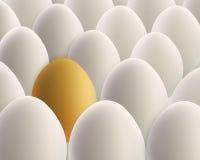 在白鸡蛋之间的唯一金黄鸡蛋 免版税库存图片