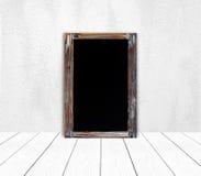 在白水泥墙壁上的空白的葡萄酒粉笔板 免版税库存照片
