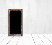 在白水泥墙壁上的空白的葡萄酒粉笔板 库存图片