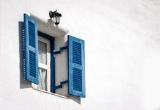 在白水泥墙壁上的蓝色葡萄酒窗口 库存照片