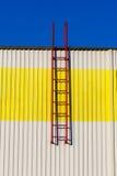 在白黄色墙壁上的红色梯子。 图库摄影