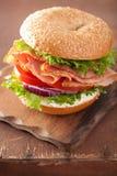 在百吉卷的火腿三明治用乳脂干酪蕃茄葱 库存图片