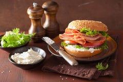 在百吉卷的火腿三明治用乳脂干酪蕃茄葱 免版税库存照片