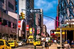 在百老汇的街道风景在曼哈顿, NYC 与交通的图片和小室和著名剧院、音乐广告和billdboards 免版税库存照片