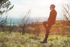 在的一个人在与帽子和运动鞋坐slackline,抓住的玻璃岁平衡并且享有在的生活 图库摄影