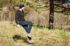 在的一个人在与帽子和运动鞋坐slackline,抓住的玻璃岁平衡并且享有在的生活 免版税库存图片