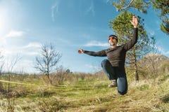 在的一个人在与帽子和运动鞋坐slackline,抓住的玻璃岁平衡并且享有在的生活 库存图片