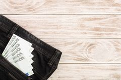 在的一百张欧洲钞票牛仔裤在与拷贝空间的白色木背景装在口袋里您的文本的 顶视图 免版税库存照片
