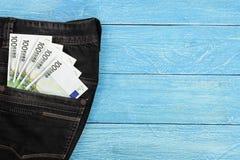 在的一百张欧洲钞票牛仔裤在与拷贝空间的蓝色木背景装在口袋里您的文本的 顶视图 库存图片