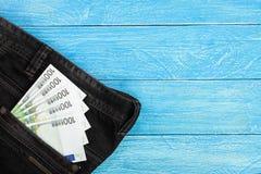 在的一百张欧洲钞票牛仔裤在与拷贝空间的蓝色木背景装在口袋里您的文本的 顶视图 库存照片