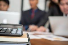 在的书桌&开的商人上的计算器会议 Businessm 库存图片